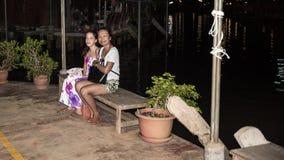Kobieta i nastoletni obsiadanie na ławce przy nocą przy spławowym rynkiem zdjęcia stock