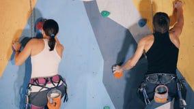 Kobieta i obsługuje wspinaczkową ścianę, zamyka w górę zbiory