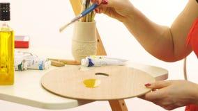 Kobieta impregnuje paletę dla nafcianych farb Artysta przygotowywa sztalugę dla rysować Piękny olej dla impregnaci zbiory