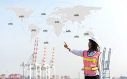 Kobieta inżynier pracuje z zbiornika ładunku zafrachtowań statkiem w stoczni przy półmrokiem dla Logistycznie importa eksporta tł Obraz Stock
