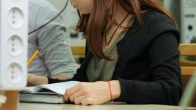 Kobieta inżyniera uczeń przystosowywa elektrycznego generator ręką Ja zmienia liczby na przyrządzie i ostrożnie zbiory