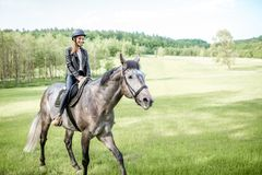 Kobieta jeździecki koń na zielonej łące obraz royalty free