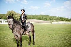 Kobieta jeździecki koń na zielonej łące obrazy stock