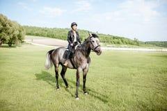 Kobieta jeździecki koń na zielonej łące zdjęcie royalty free