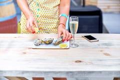 Kobieta je świeże ostrygi na talerzu Obrazy Stock