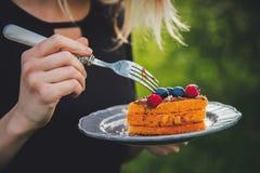 Kobieta je czekoladę zakrywał czarnej jagody i malinki pika tort zdjęcia royalty free