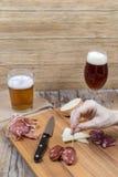 Kobieta je drewnianą deskę z kiełbasy, sera i piwa glasse, Fotografia Royalty Free