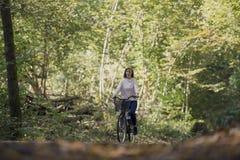 Kobieta jeździecki bicykl w lesie Zdjęcie Royalty Free