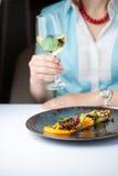 Kobieta je ośmiornicy i pije wino w restauraci Obrazy Royalty Free