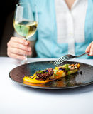 Kobieta je ośmiornicy i pije wino w restauraci Obrazy Stock