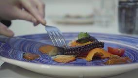 Kobieta je pięknie słuzyć apetyt ośmiornicy i piec na grillu świeżych warzyw na błękitnym talerzu z bliska zbiory wideo
