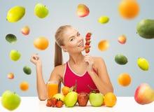 Kobieta je truskawki z sokiem i owoc Fotografia Stock