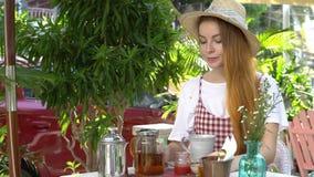 Kobieta je truskawkowego dżem podczas gdy pijący herbaty Herbaciany garnek, miód na stole zbiory wideo