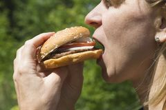 kobieta jedzenia hamburgera obraz royalty free