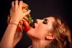 kobieta jedzenia hamburgera Uczeń spożywa fast food Zdjęcia Royalty Free