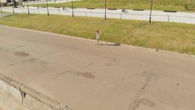 Kobieta jedzie hulajnogę outdoors w lecie Powietrzna strzelanina zbiory