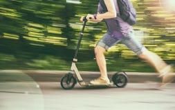 Kobieta jedzie hulajnoga przy prędkość puszkiem drogowy, zamazany backgroun, Fotografia Royalty Free