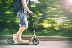 Kobieta jedzie hulajnoga przy prędkość puszkiem drogowy, zamazany backgroun, Fotografia Stock
