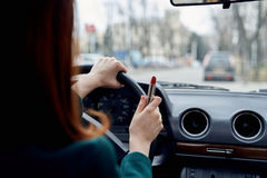 Kobieta jedzie jej samochód trzyma czerwoną pomadkę w mieście obraz stock