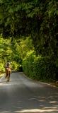 Kobieta jedzie konia na ulicznym, wiejskim miasteczku, zielone rośliny Obrazy Stock
