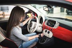 Kobieta jedzie samochód i zwrota guzika na deska rozdzielcza panelu w samochodzie nowego i nowożytnego obraz royalty free
