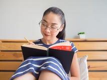 Kobieta jest czytelniczym książką na łóżku fotografia royalty free