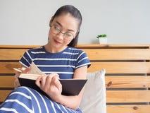 Kobieta jest czytelniczym książką na łóżku obraz royalty free
