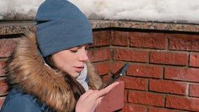 Kobieta jest obcojęzycznym audio wiadomością na telefonu komórkowego obsiadaniu w zima parku Zbliżenie twarzy boczny widok zdjęcie wideo