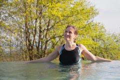 Kobieta jest odpoczynkami w plenerowym basenie Fotografia Royalty Free