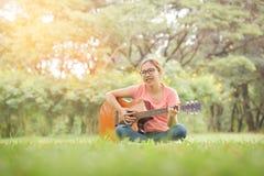 Kobieta jest siedząca gitarę akustyczną i bawić się Fotografia Royalty Free