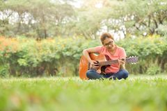 Kobieta jest siedząca gitarę akustyczną i bawić się Obrazy Royalty Free