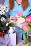 Kobieta jest ubranym błękitną bluzkę komponuje bukiet tulipany i chryzantemy obraz royalty free
