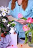 Kobieta jest ubranym błękitną bluzkę komponuje bukiet tulipany i chryzantemy obraz stock