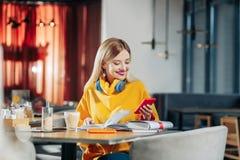 Kobieta jest ubranym błękitne słuchawki czyta wiadomość na telefonie obraz royalty free