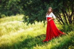 Kobieta jest ubranym czerwieni spódnicową pozycję pod drzewem Fotografia Stock