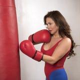 Kobieta jest ubranym czerwone bokserskie rękawiczki uderza pięścią torbę zdjęcia royalty free