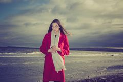 Kobieta jest ubranym czerwonego żakiet na seashore fotografia stock