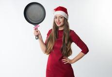 Kobieta jest ubranym czerwonego Santa Claus kapelusz z prezentem smaży nieckę Zdjęcie Royalty Free