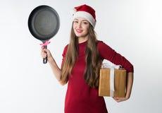 Kobieta jest ubranym czerwonego Santa Claus kapelusz z prezentem smaży nieckę Zdjęcia Stock