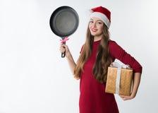 Kobieta jest ubranym czerwonego Santa Claus kapelusz z prezentem smaży nieckę Fotografia Stock