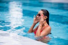 Kobieta jest ubranym czerwonego swimsuit i okulary przeciwsłonecznych siedzi w pływackim basenie, dotyka mokrego włosy Zdjęcia Royalty Free