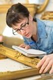 Kobieta jest ubranym eyeglasses egzamininuje antykwarsk? obrazek ram? zdjęcie royalty free