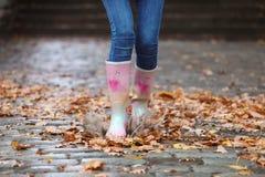 Kobieta jest ubranym gumowych buty bryzga w kałuży po deszczu fotografia stock