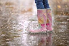 Kobieta jest ubranym gumowych buty bryzga w kałuży po deszczu, ostrość na nogach obrazy stock