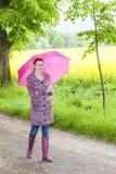 Kobieta jest ubranym gumowych buty z parasolem Zdjęcia Stock