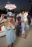 Kobieta Jest ubranym kapelusz Z przyjaciółmi I Elvis Presley parodystą W tle zdjęcie stock
