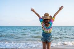Kobieta jest ubranym kapelusz z ręka podnoszącą pozycją na morze plaży obrazy stock