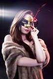 Kobieta jest ubranym karnawałową venetian maskę na plamy tle.   Obrazy Stock