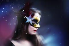 Kobieta jest ubranym karnawałową venetian maskę na plamy tle.   Zdjęcie Stock