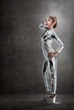 Kobieta jest ubranym lateksowego kombinezon pozuje nad grunge tłem Zdjęcia Stock